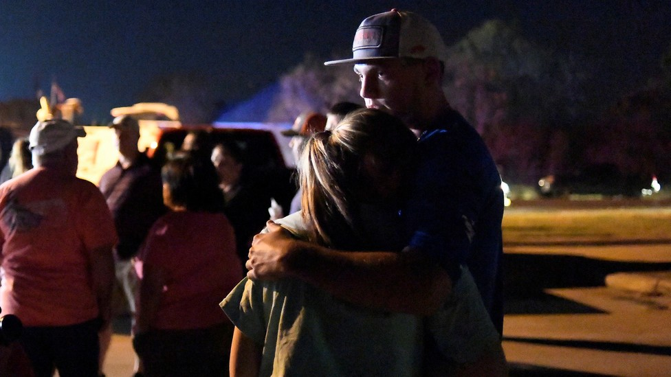 Two people embrace at a nighttime vigil.