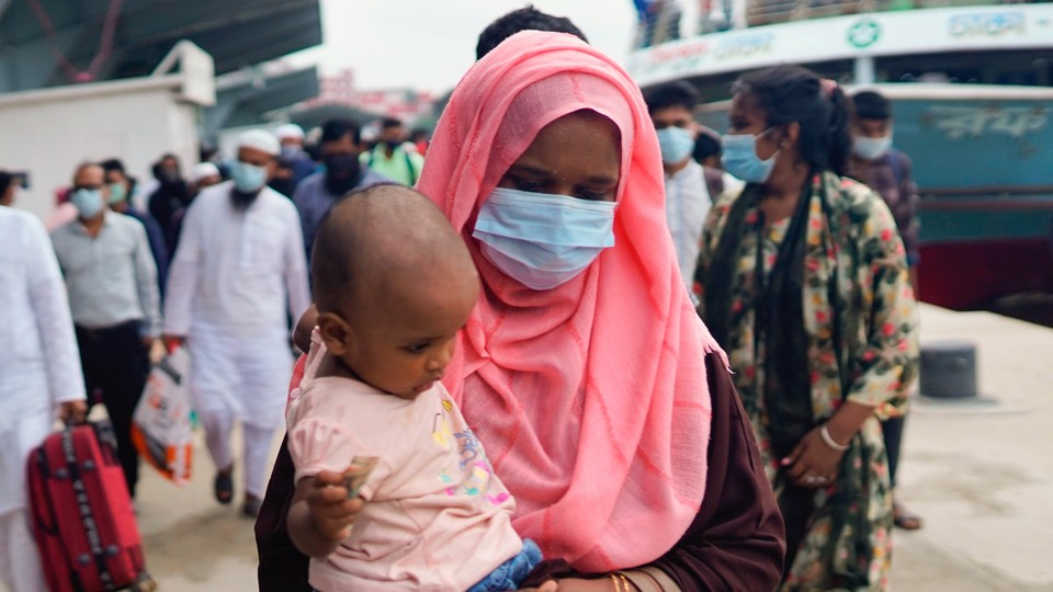 A photograph of a mask-wearing woman carrying a child.