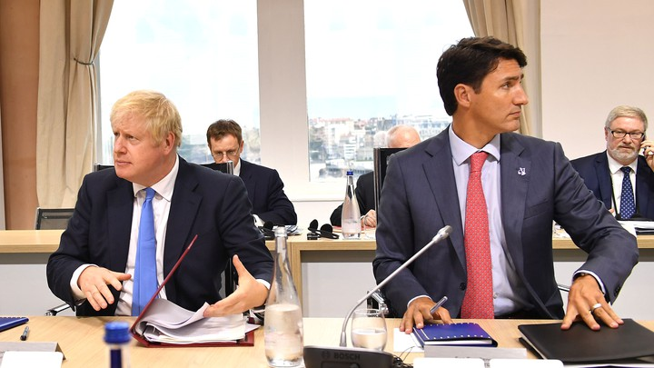 Boris Johnson and Justin Trudeau sit alongside each other at a table.