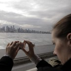 A photo of a tourist taking a photo of the Vancouver skyline.