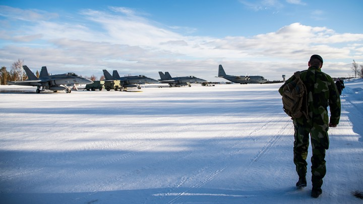 A soldier approaches planes on an icy field.