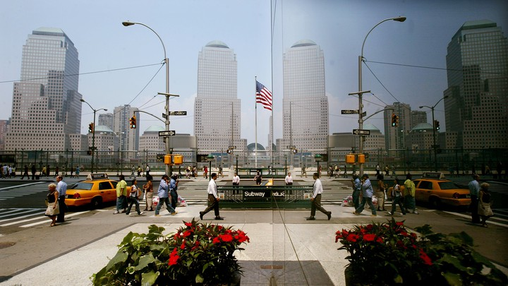 Pedestrians in New York are reflected in a window as they pass the World Trade Center site.