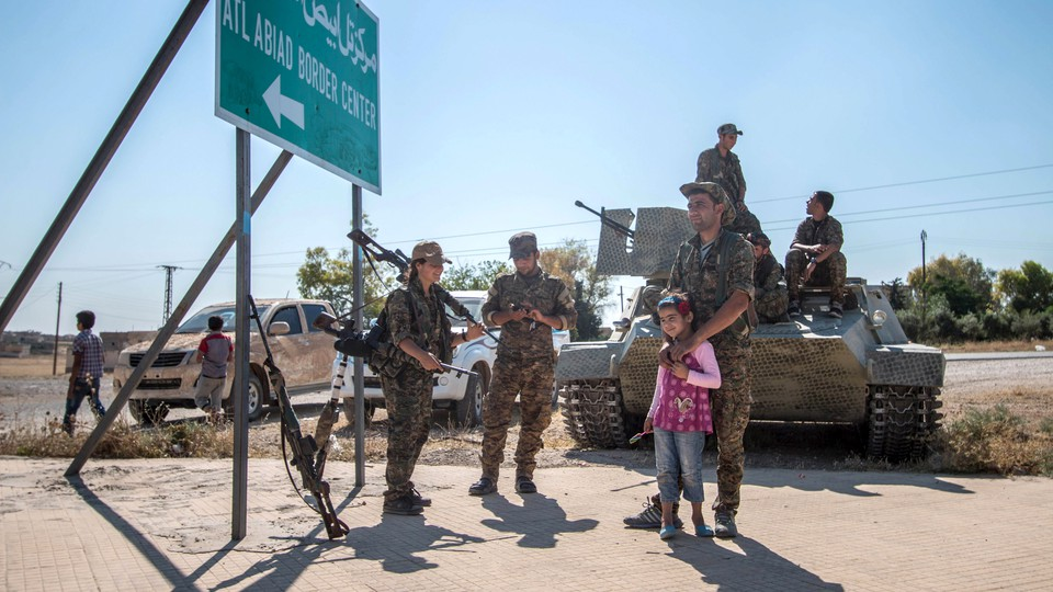 YPG fighters stand with a child near a tank in Raqqa in 2015