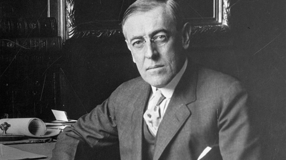 An archival photo of Woodrow Wilson sitting at a desk