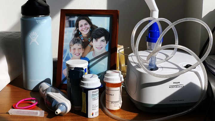 A photo of a framed family photograph, a nebulizer, a Hydro Flask, and bottles of pills on a desk