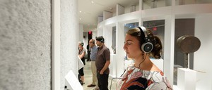 Museum visitors standing in a padded gallery wearing big headphones and closing their eyes