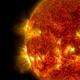 The sun as a fiery red balls spewing particles