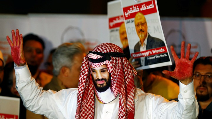A demonstrator wearing a mask of Saudi Crown Prince Mohammed bin Salman attends a protest outside the Saudi consulate. In the background, other demonstrators hold signs with pictures of Jamal Khashoggi.