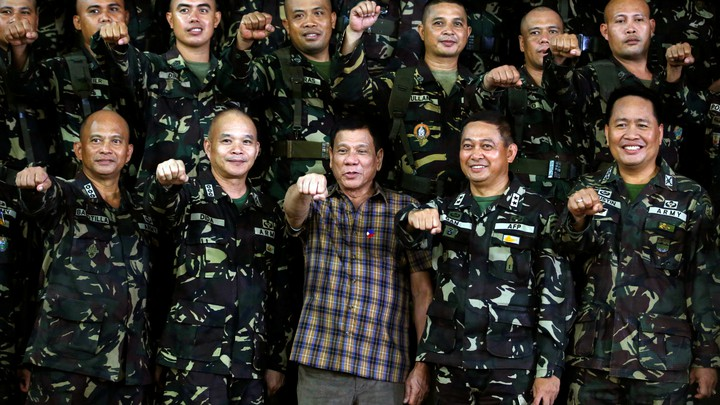 """Philippine President Rodrigo Duterte makes a """"fist bump"""", his May presidential elections campaign gesture, with soldiers during a visit at Capinpin military camp in Tanay, Rizal in the Philippines August 24, 2016."""