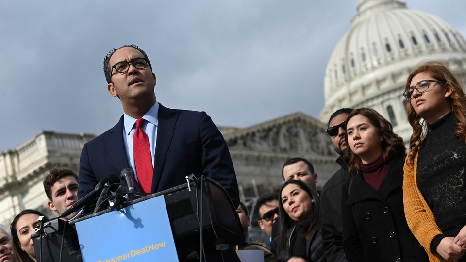Representative Will Hurd of Texas stands at a podium outside the U.S. Capitol in Washington, D.C. Behind him are 10 men and women watching him speak. The Capitol dome is visible in the background.