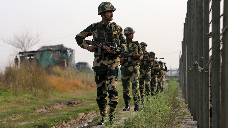 India's Border Security Force soldiers patrol along the fenced border with Pakistan on February 26, 2019.
