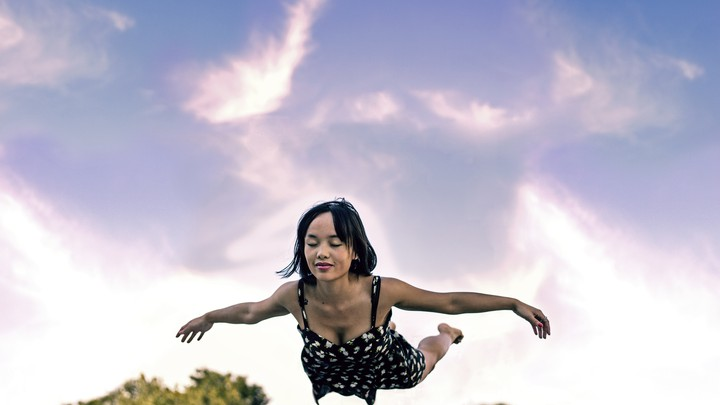 A woman with eyes closed suspended in mid-air