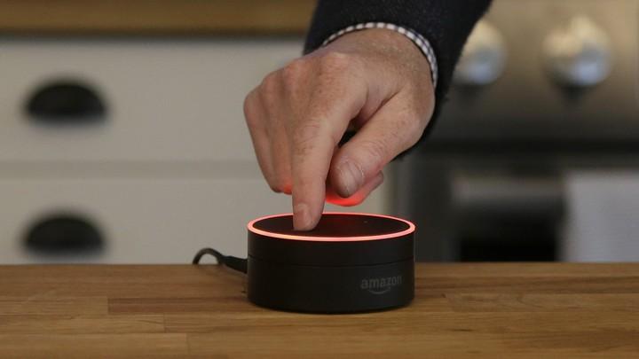 A man mutes an Amazon Echo Dot