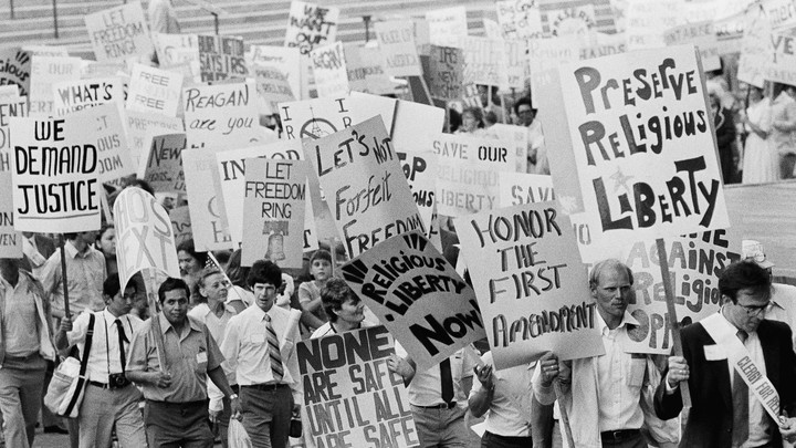 """A black-and-white photo of a Reagan-era protest in front of the Supreme Court's steps, with signs reading """"Preserve religious liberty"""" and """"Honor the First Amendment"""""""