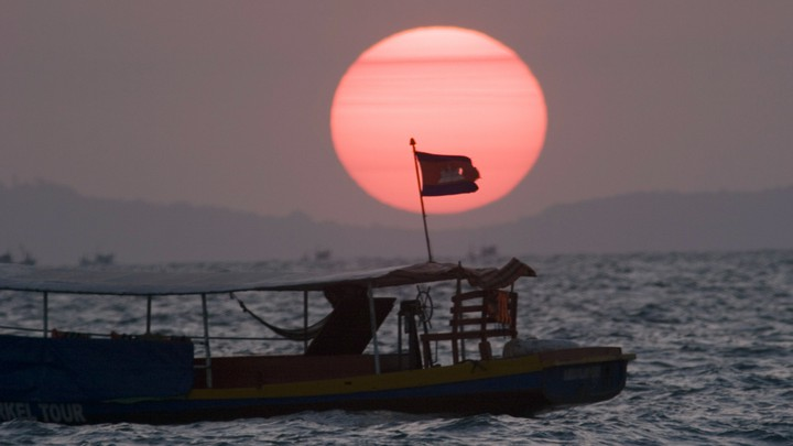 A fishing boat near Sihanoukville flies the Cambodian flag.