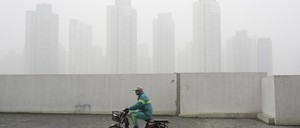 a photo of a man on an electric bike riding through heavy smog in Shanghai, China.
