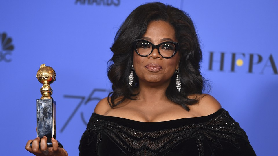 Oprah Winfrey stands with her Golden Globes award.
