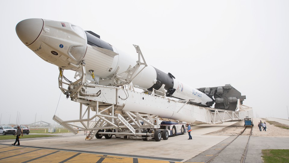 A SpaceX Falcon 9 rocket, with the company's Crew Dragon spacecraft onboard, on its way to the launchpad