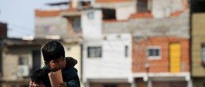 A man with a small boy on his shoulders walks through Villa 31, an informal settlement in Buenos Aires.