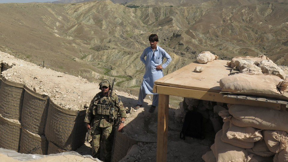 A U.S. soldier stands at a post in Nangarhar province alongside an Afghan civilian.