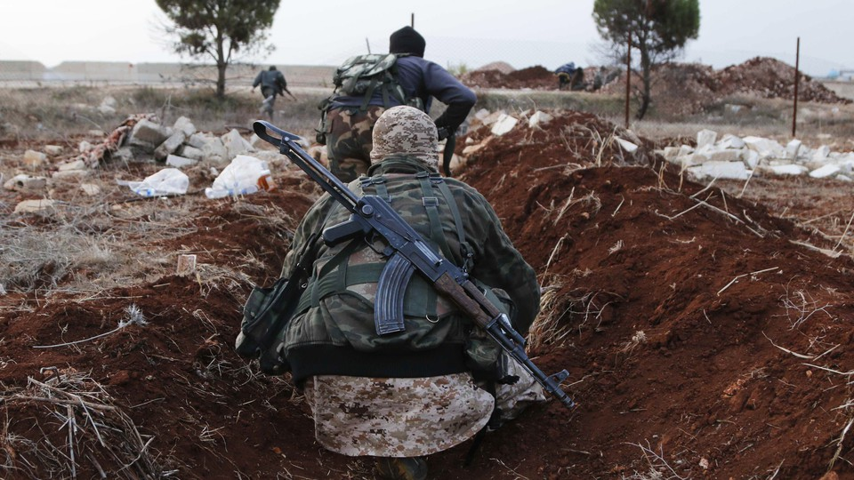 Two members of al-Qaeda's Nusra Front in Syria hold weapons while standing in a ditch.