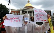 A woman wearing a face shield, surgical mask, and plastic poncho holds up signs in protest of school reopening.