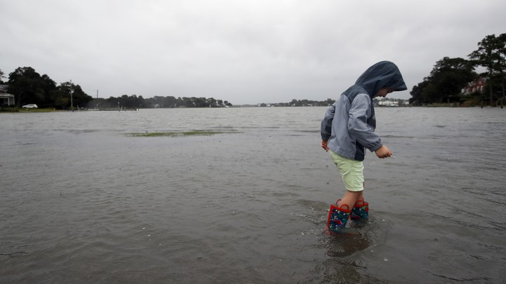 A boy wearing rainboots wades through the ankle-high water in Norfolk, Virginia.