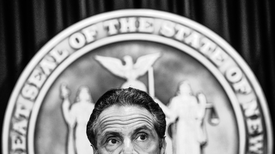 The top half of New York governor Andrew Cuomo's head is shown in front of the seal of the state of New York.