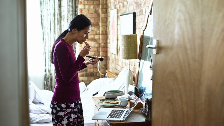 A woman eats and does her makeup while looking at a laptop.