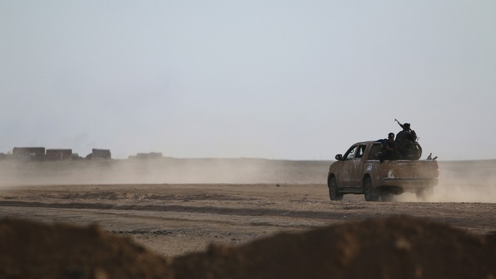 A pickup truck drives on a dusty road toward structures in the distance.