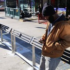 People use leaning bars at a bus stop in Brooklyn in 2016.