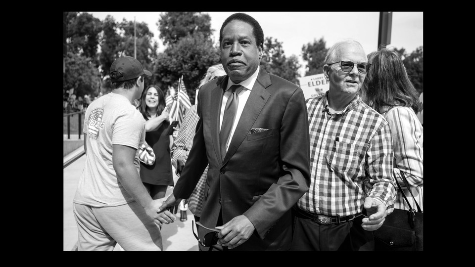 black-and-white photo of Larry Elder in a small crowd