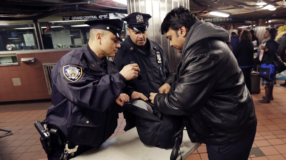 Police officers inspect a bag in a New York subway station.
