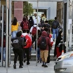 A group of high school students walk through the campus gates