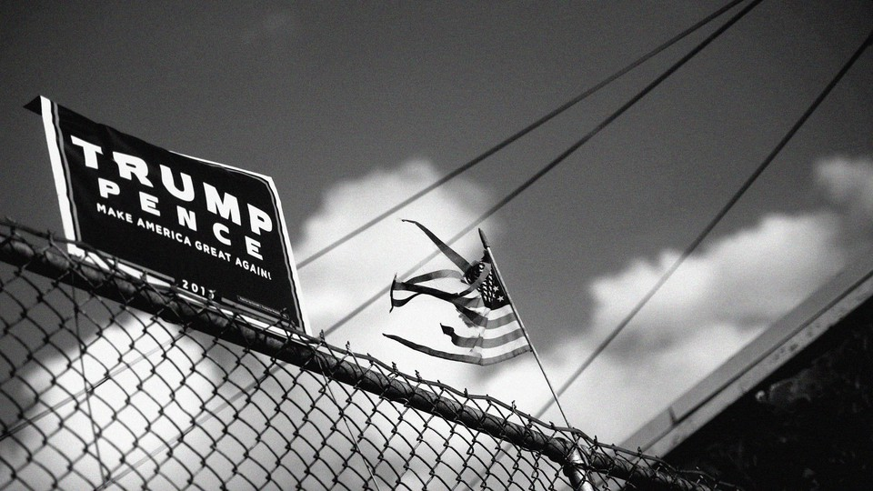 A Trump-Pence campaign sign on a fence with an American flag in the background