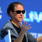A photo of Anne Wojcicki, CEO and co-founder of 23andMe, speaking at a conference.