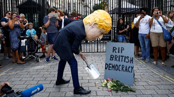 """A man wearing a Boris Johnson mask stands outside Downing Street, pretending to dig a grave for """"British Democracy."""""""
