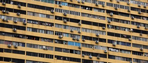 The outside of a large apartment building, dotted with air conditioners.