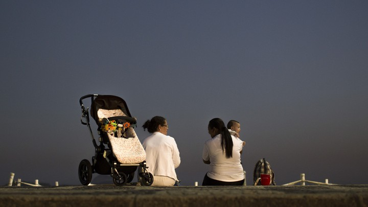 Two domestic workers chat as they take care of a baby at Leblon beach in Rio de Janeiro, Brazil.