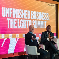 "Two men at The Atlantic Festival in front of a sign that reads ""Unfinished Business: The LGBTQ Summit."""