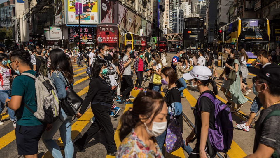 People wear masks at a crowded intersection in Hong Kong.