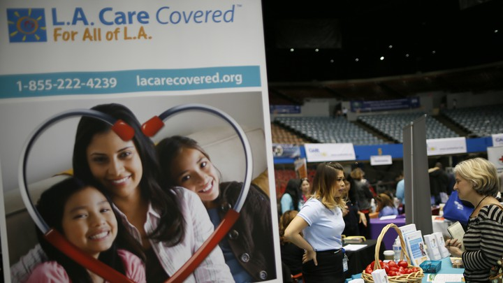 Two women converse behind a sign for the L.A. Care Health Plan.