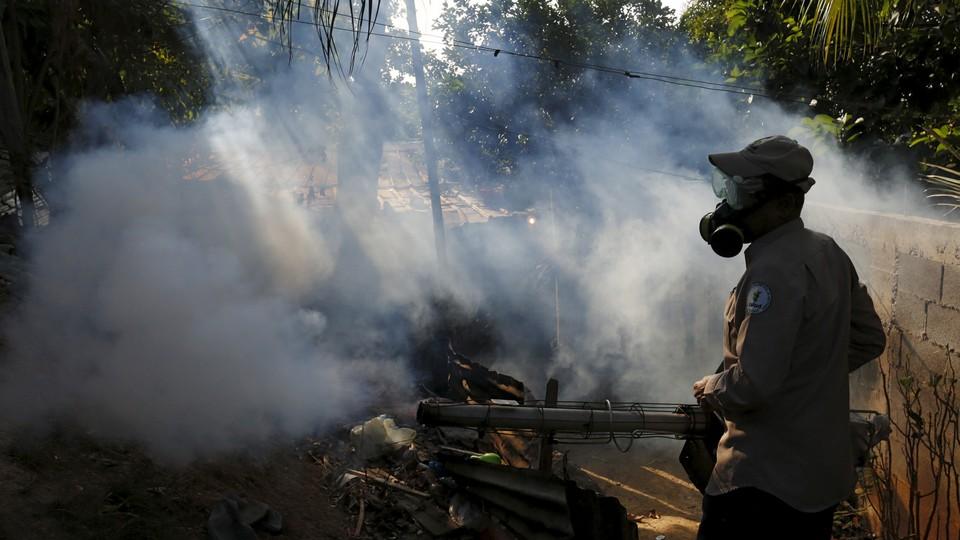 A health worker fumigates a neighborhood on the outskirts of Panama City