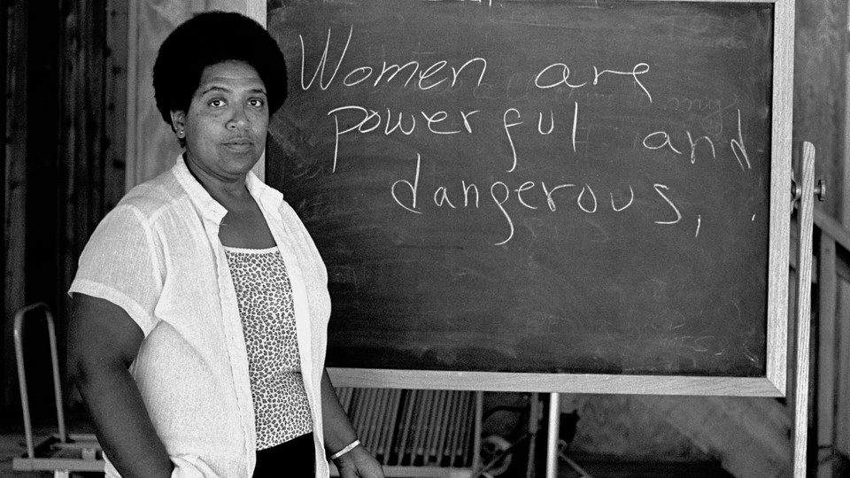 """Audre Lorde in front of a blackboard that reads: """"Women are powerful and dangerous."""""""