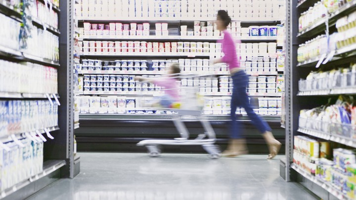 A mother pushes her child through a grocery store