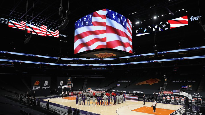 A basketball arena  with the players standing in a circle around center court and video screens showing the American flag above empty stands