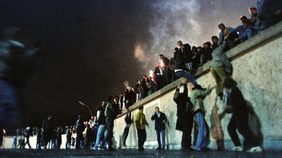 West Berliners help East Germans over the Berlin Wall.