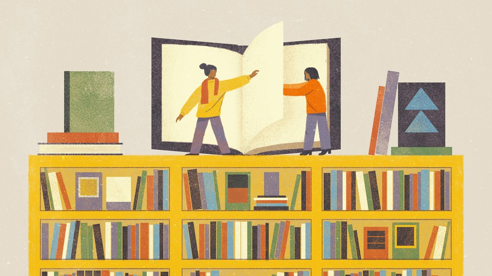 Two women stand on top of a huge bookshelf, helping each other turn the page of a large book