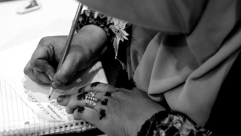 A woman wearing a headscarf writes English letters on paper.