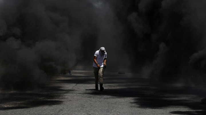 A protester crouching in black smoke